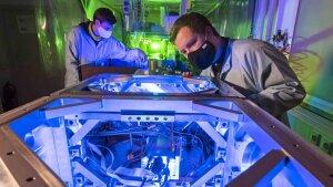 Dr. Frederik Tuitje (r.) und Tobias Helk bereiten die Laser-Plasma-Quelle für Experimente vor.